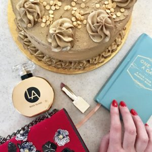 A flat lay of a cake, perfume, blue book and red lipstick.