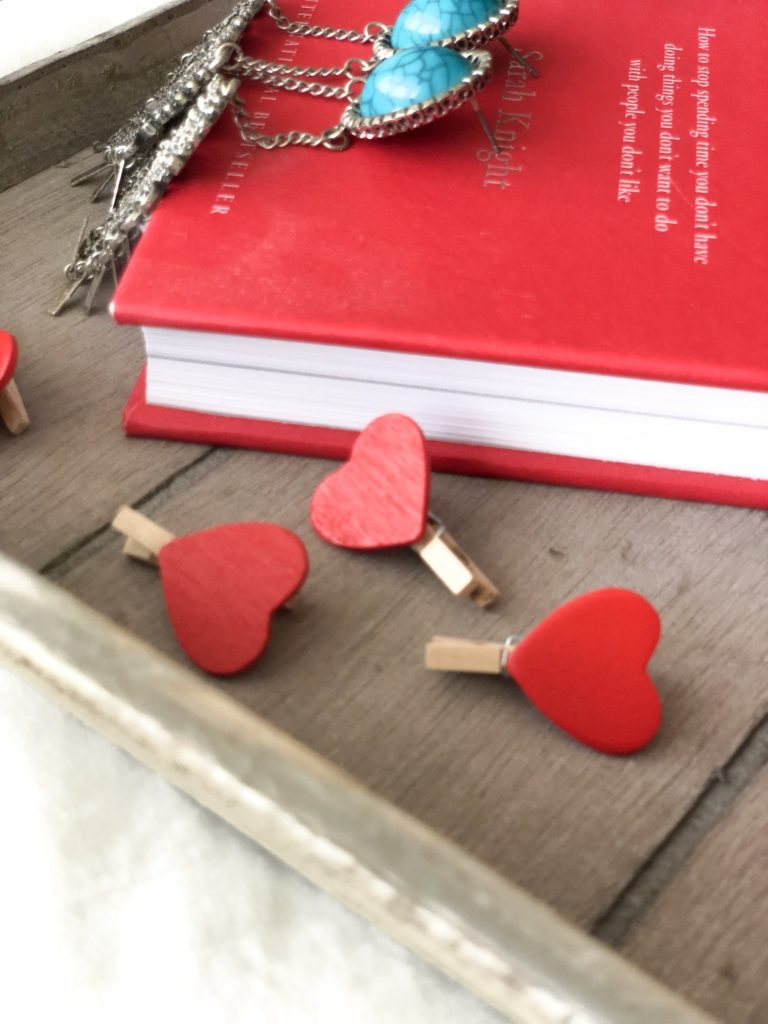 A flat lay showing a red book covered in red love hearts