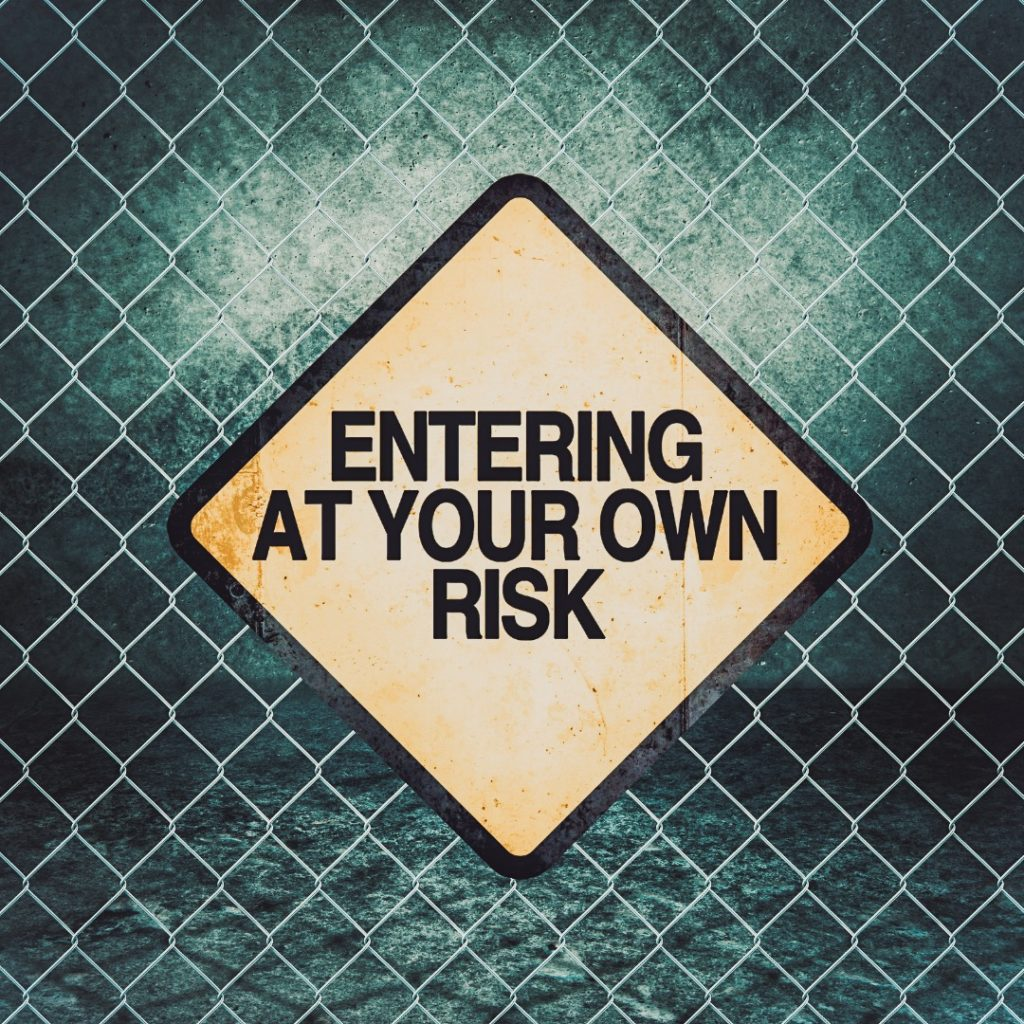 A sign on a fence saying - Entering at your own risk