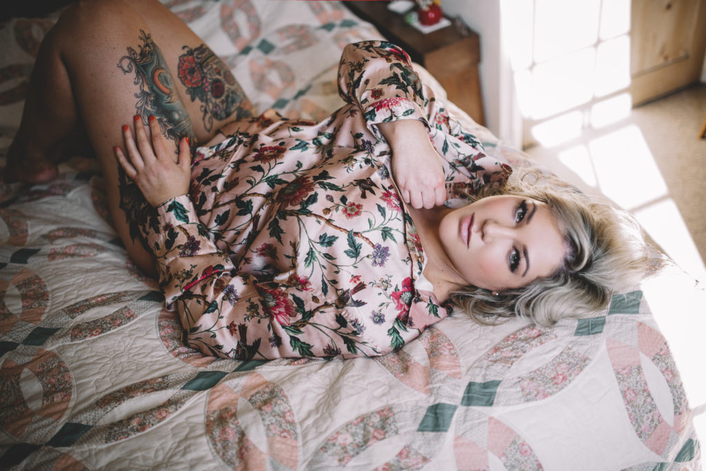 Cara lays on a bed in a shirt looking confident